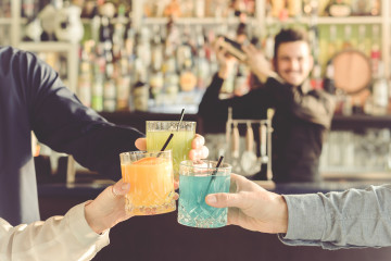 three friends are toasting with their drinks in hand during a party while the barman is shaking - people, drinks, party and lifestyle concept